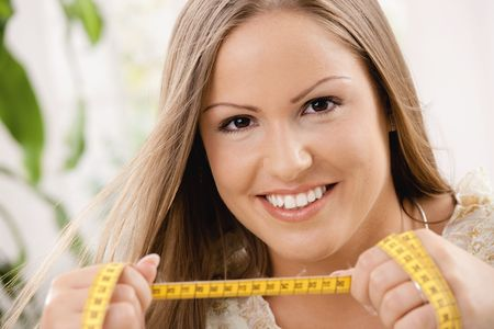 'tape measure': Happy young woman on diet holding tape measure, smiling. Stock Photo