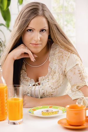 Young woman on diet sitting at table, thinking over tape measure on plate. Stock Photo - 5071132