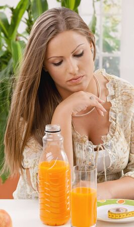 Young woman on diet sitting at table, thinking over tape measure on plate. photo
