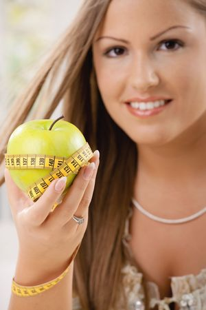 Happy young woman showing apple and tape measure, smiling. photo