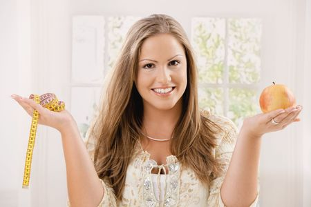 Happy young woman holding apple and tape measure, smiling. photo
