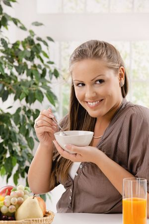 Happy young woman eating breakfast cereal and drinking orange juice, smiling. photo