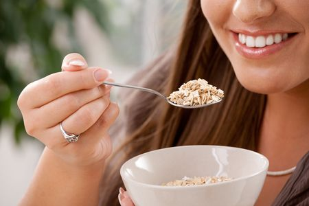 partially: Closeup of partially visible young woman eating breakfast cereal. Selective focus on spoon. Stock Photo