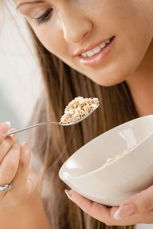 Beautiful young woman eating breakfast cereal. Selective focus on spoon. photo
