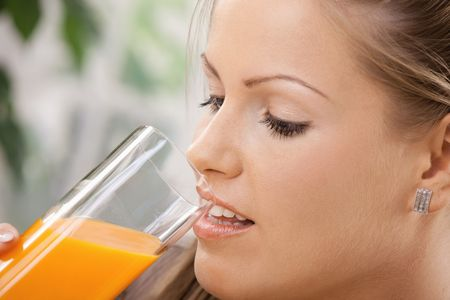 Closeup portrait of beautiful young woman drinking orange juice. photo