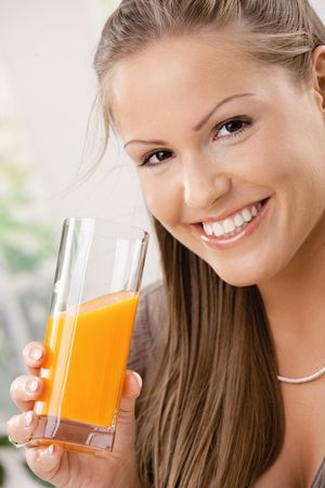 Closeup portrait of beautiful young woman drinking orange juice. Stock Photo - 5071106
