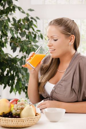 Young woman sitting at table having breakfast, drinking orange juice. Stock Photo - 5071137