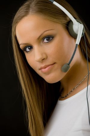 Young happy beautiful customer service operator girl in headset, smiling, isolated on black background. photo