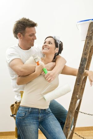 Happy couple doing home improvement. Holding painting tools, hugging and smiling to each other.  photo