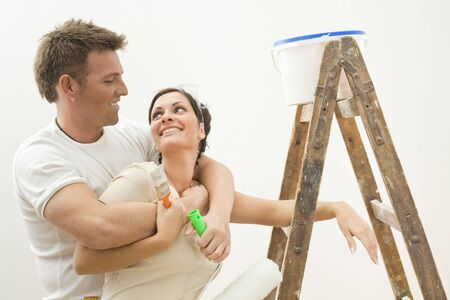 Happy couple painting their new home. Holding tools, hugging and smiling to each other.  photo