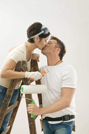Young couple standing on ladder in new home, holding painting tools, kissing. Isolated on white background. photo