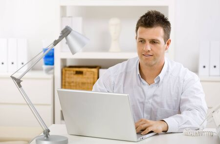undoubting: Casual young businessman working at home on laptop compuer, looking at screen.