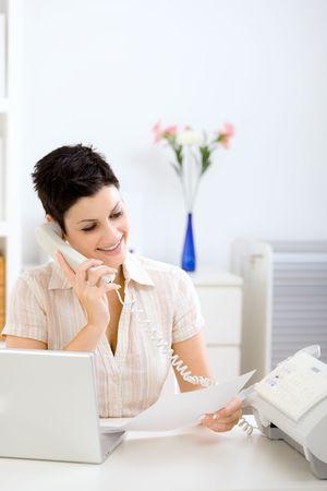 sending: Casual joven empresaria de trabajo en el hogar, la lectura de un fax y hablar por tel�fono. Foto de archivo