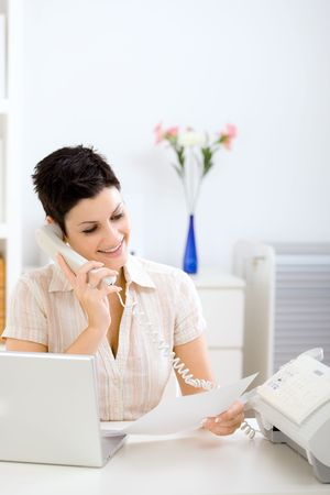 open shirt: Casual young businesswoman working at home, reading a fax and talking on phone.