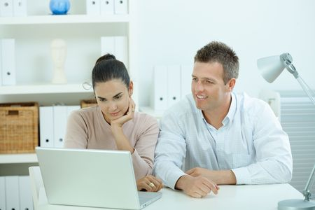 sinecure: Young casual couple sitting  at desk working together at home office, smiling, happy, using laptop computer.