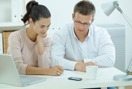outwork: Feliz joven casual joven sentado a trabajar juntos en la mesa de oficina en casa, sonriendo.