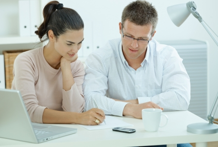 outworking: Happy young casual couple sitting  at desk working together at home office, smiling.