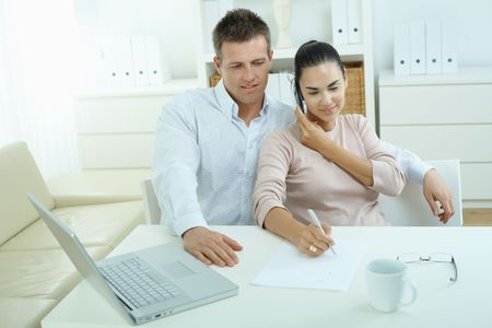 teleworking: Couple working on laptop computer at home office, happy, smiling. Woman calling on mobile phone. Stock Photo