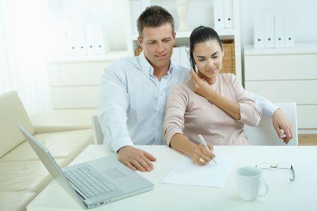 outwork: Mayor trabajo en equipo port�til de oficina en casa, felices, sonrientes. Mujer pide a tel�fono m�vil.