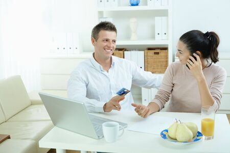 room card: Young couple sitting at desk shopping on internet from home. Calling phone, using laptopcomputer and paying with credit card.