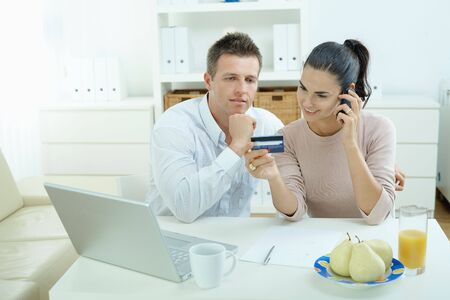 Young couple sitting at desk shopping on internet from home. Calling phone, using laptopcomputer and paying with credit card. Stock Photo - 5101748