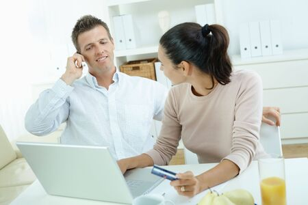 Young couple sitting at desk shopping on internet from home. Calling phone, using laptopcomputer and paying with credit card. Stock Photo - 5102008