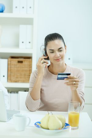 Woman sitting at desk at home purchasing with credit card and cell phone. photo
