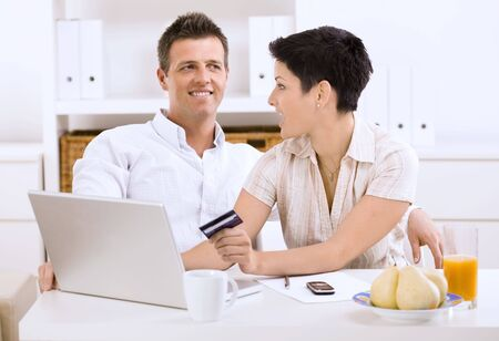 Happy young couple shopping online at home using laptop computer, looking each other. Stock Photo - 5101522