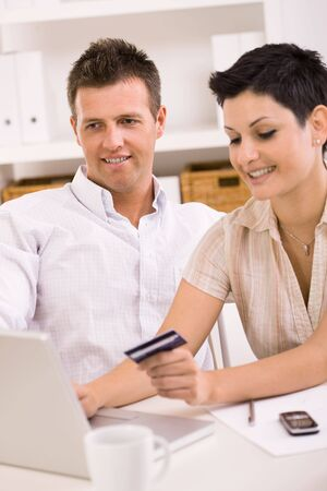 Happy young couple paying with credit card at home. Stock Photo