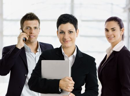 Team portrait of young businesspeople, posing in office lobby, smiling.  Woman standing in front, holding laptop computer. Man taling on mobile phone in background. photo