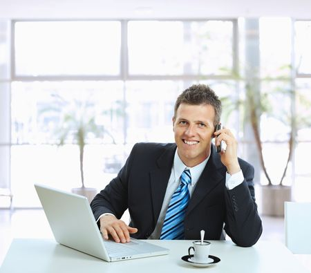Businessman sitting at table in office hall, talking on mobile phone and using laptop computer, smiling.