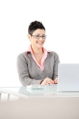 stitting: Happy businesswoman stitting at office desk using laptop computer, smiling. Isolated on white background.