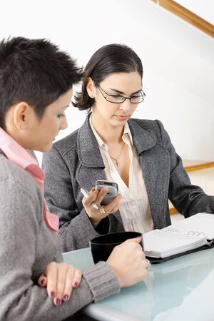 Young businesswomen sitting at office desk, working and talking. Stock Photo - 5102051