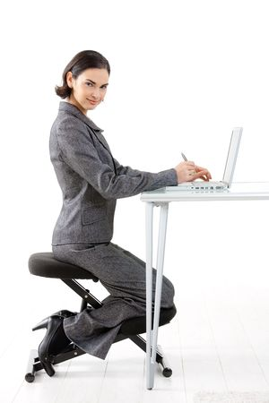 Young happy businesswoman working on kneeling chair, smiling, isolated on white. photo
