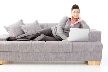 Woman lying on sofa at home working on laptop computer. Isolated on white background. photo