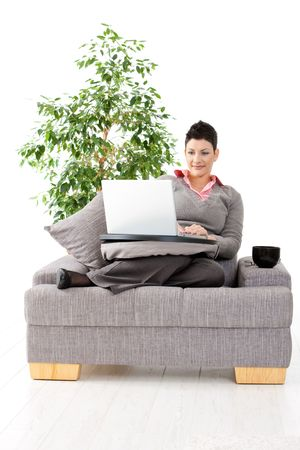 Young woman sitting on couch working on laptop computer at home, smiling. White background with green plant. Stock Photo - 5101779