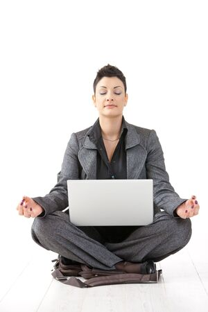 Young businesswoman sitting in yoga lotus position, holding laptop computer, meditating with closed eyes, isolated. photo