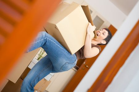 lift and carry: Woman lifting cardboard box while moving home, smiling.