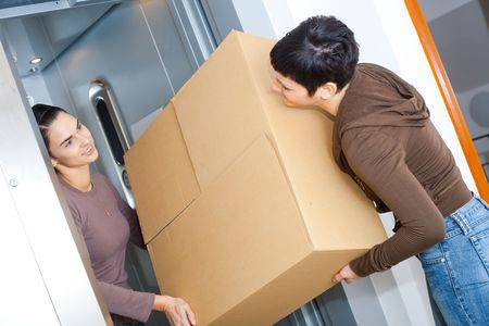 people in elevator: Two happy women moving cardboard box with elevator, smiling.