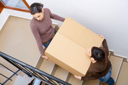 Two young women carrying up cardboard box on stariway to new home. Stock Photo