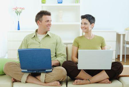 outwork: Feliz pareja de j�venes sentados en el sof� en casa con ordenador port�til, sonriendo. Foto de archivo