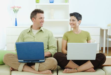sinecure: Happy young couple sitting on couch at home using laptop computer, smiling.