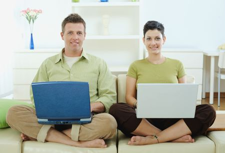 outworking: Happy young couple sitting on couch at home using laptop computer, smiling.