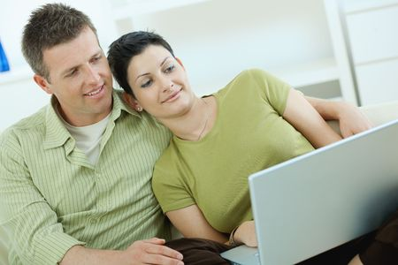 Young couple sitting on couch at home and using laptop computer. Stock Photo - 5183014