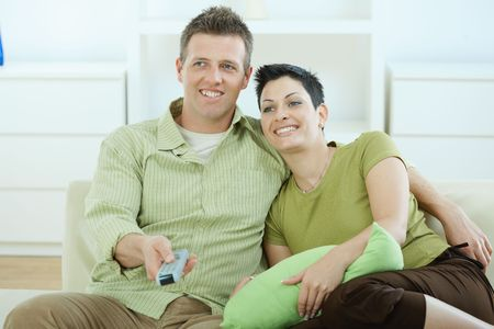 Young couple watching TV at home sitting pn sofa. photo