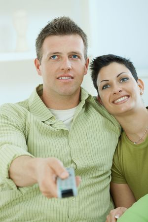 Young couple watching TV at home sitting pn sofa. Stock Photo - 5183047