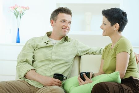 Young couple drinking coffee at home, sitting on couch, looking at each other, smiling. Stock Photo - 5183046