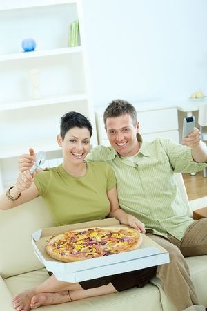 Happy couple sitting on sofa in,living room, eating pizza, smiling. photo
