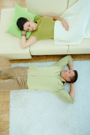 Couple sleeping at home on sofa and on floor. Overhead view. Stock Photo - 5183039