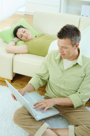Man sitting on floor at home browsing internet on laptop computer, woman sleeping on sofa. Stock Photo - 5183069